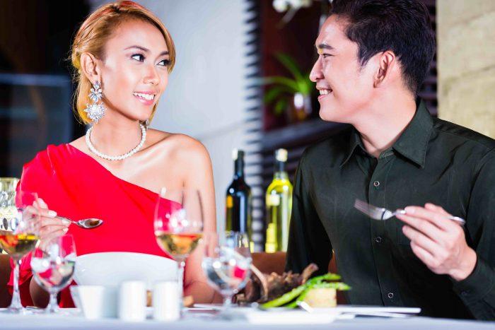 Asian couple fine dining in fancy restaurant