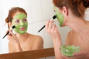 woman-putting-on-green-face-mask-home