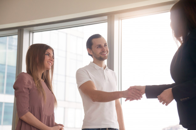 Businesswoman and clients shaking hands on business meeting