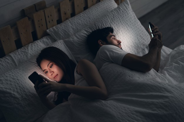 Young couple conflict in bed. happy smiling woman turned her back to man, reading message on mobile phone