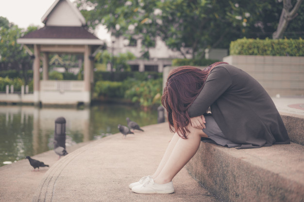 woman sitting alone and depressed, portrait of tired young woman