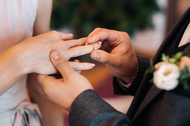 The groom puts an engagement ring on the bride's finger on their wedding day