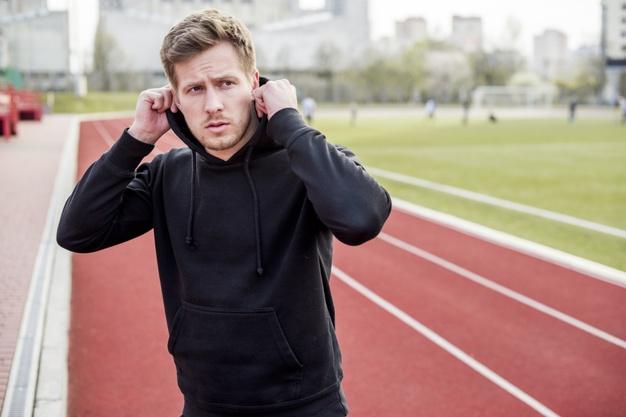 Handsome sport man wearing hoodie on race track