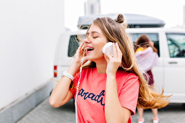 girl with trendy hairstyle in stylish pink shirt enjoying good song with smile and eyes closed