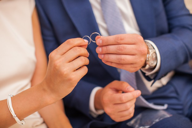 Newlywed couple holding in their fingers two wedding rings. groom and bride showing pair of bridal rings