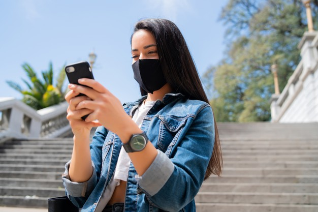 woman wearing protective mask and using her mobile phone while standing outdoors on the street