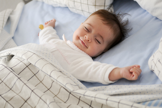 Smiling baby lying on a bed Free