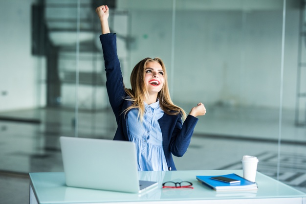 uccessful young business woman with arms up at the office