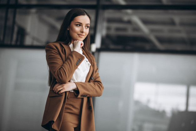 Young business woman standing in suit in office