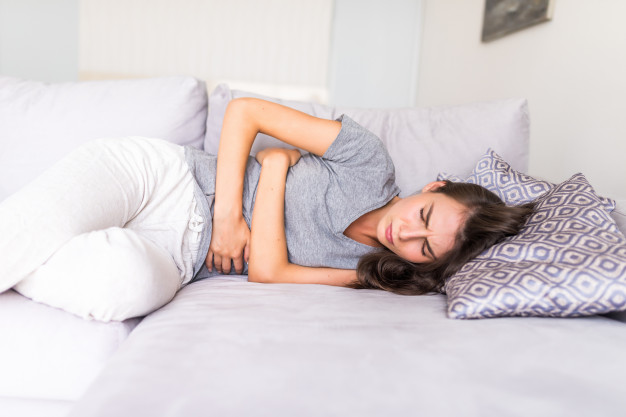 woman haviing abdominal pain because of menstruation lying in couch and holding her stomach