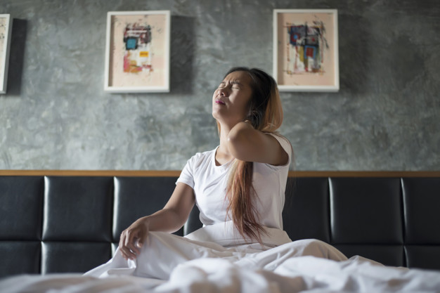 Young woman sitting on the bed with neck pain after wake up