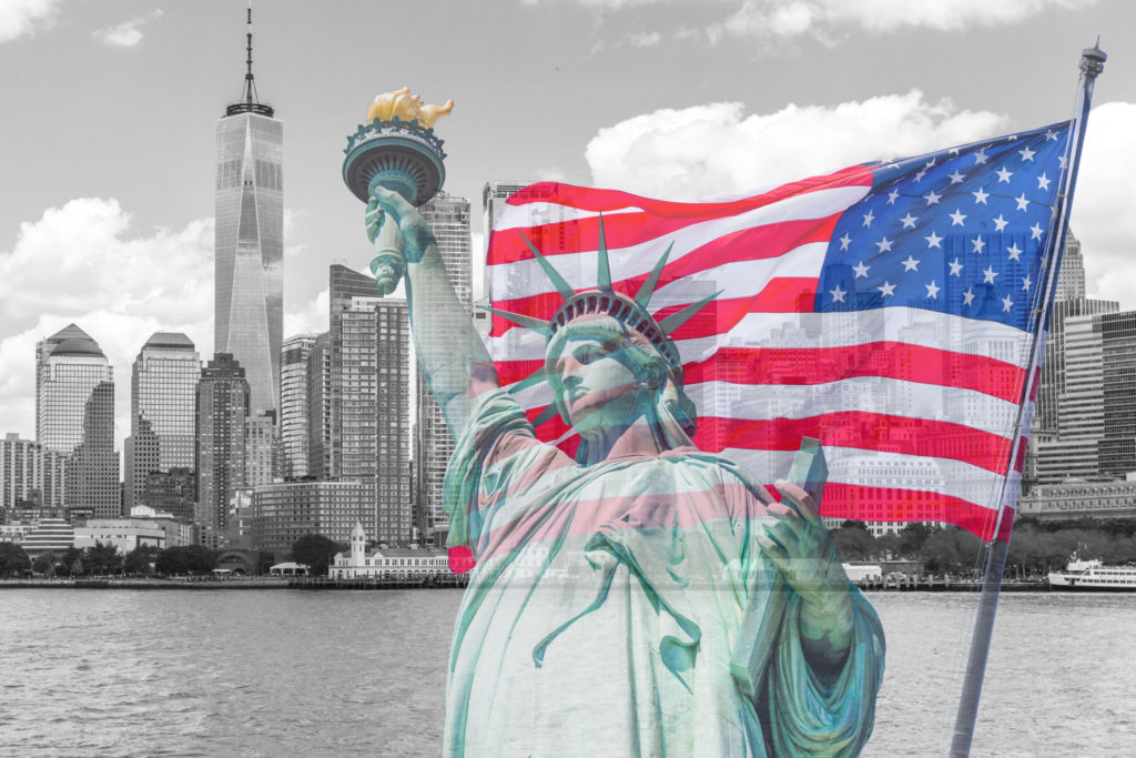Statue of liberty with a large american flag and new york skyline