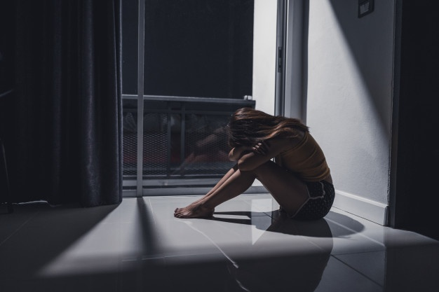 Depressed young woman sitting alone on the floor in the living room