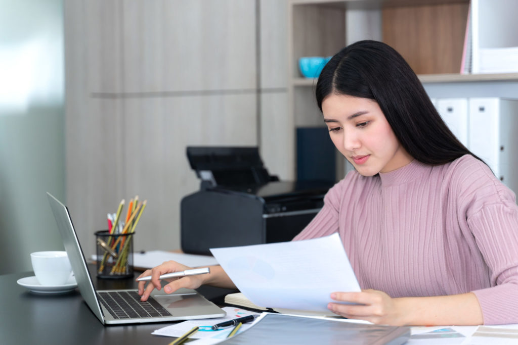 beautiful asian business young woman using laptop computer and smart phone on office desk