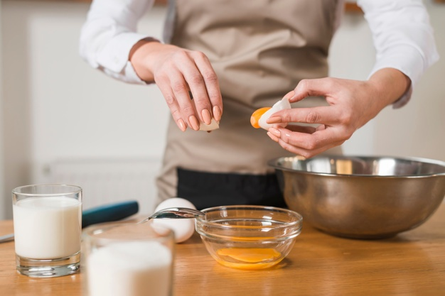 a woman putting egg yolk in the glass bowl