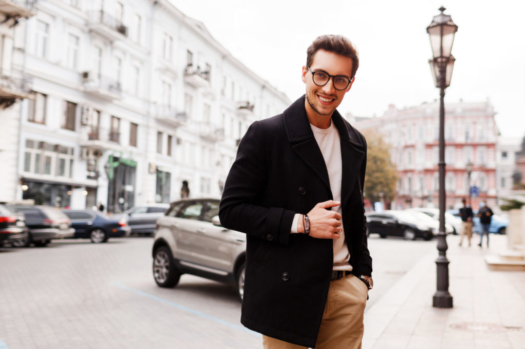 Smiling beautiful handsome man in jacket posing on the street