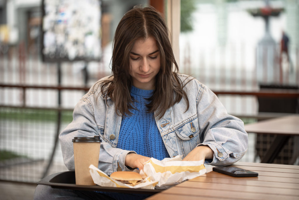 woman with fast food on the summer terrace of a cafe