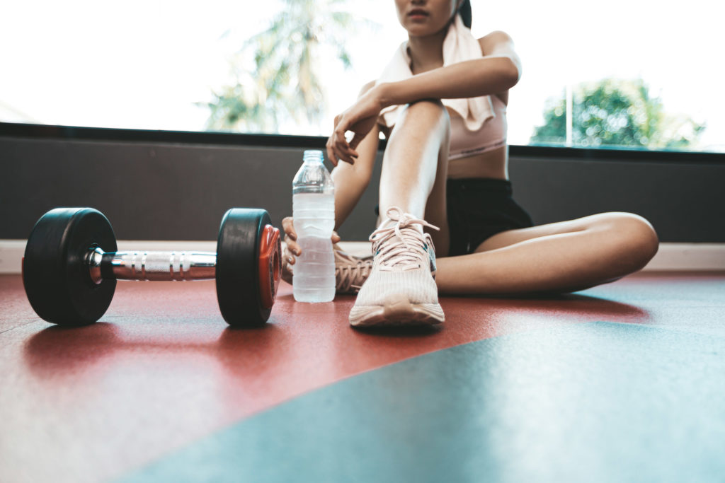 Women sit back and relax after exercise. there is a water bottle and dumbbells
