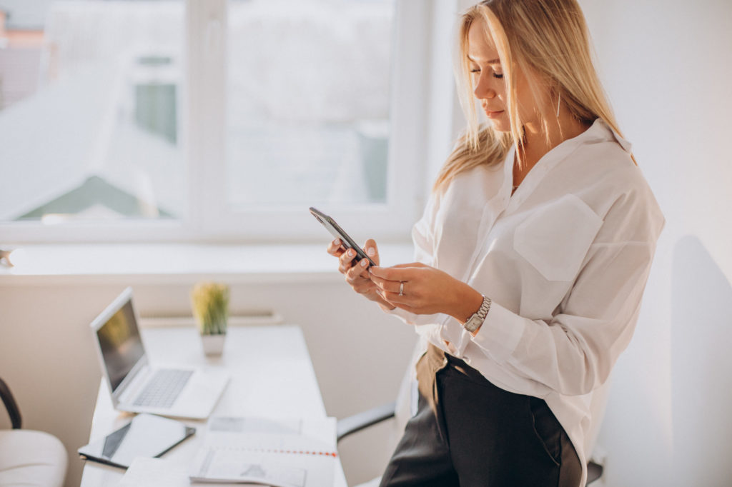 Young business woman using phone in office