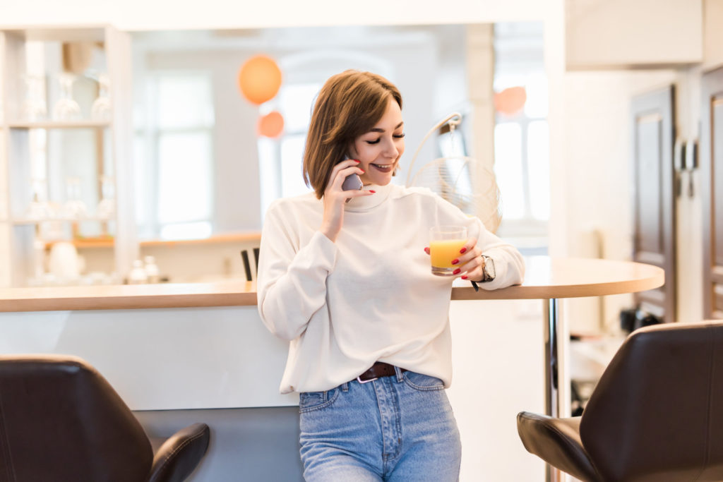 Young lady is standing near bar chair in the kitchen talking on the phone and holding a glass with orange juice